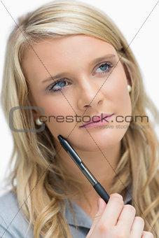 Blonde holding a pen while thinking