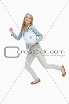 Woman running while holding a clock