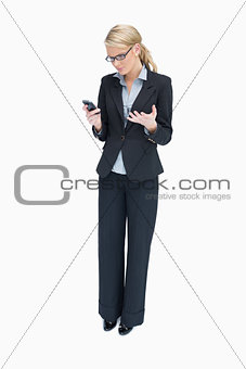 Business woman looking angrily at mobile phone