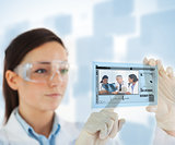 Woman pointing on picture of doctor and nurses looking at x ray on hologram interface