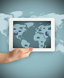 Hand holding a tablet PC showing business world map graphic