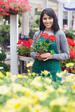 Garden center worker holding a red flower