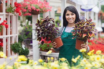 Garden center worker holding two plants while standing outside