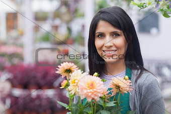 Woman holding a flower and smiling