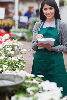 Garden center worker taking notes and smiling