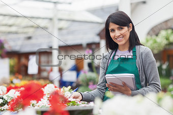 Employee taking notes in garden centre