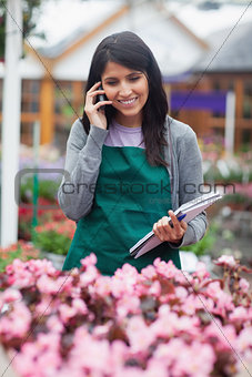 Black-haired woman calling while doing stocktaking