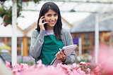 Employee talking on phone while checking flowers