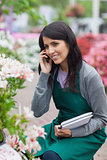 Employee doing stocktaking while calling in garden center