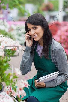 Employee doing stocktaking while calling in garden center