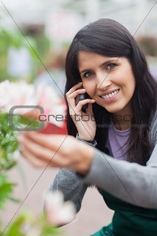 Smiling florist touching a flower and making a call