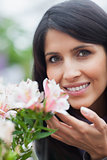 Smiling woman smelling a flower