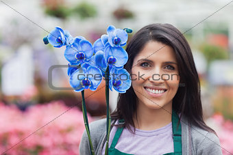 Brunette garden center worker holding a flower