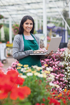 Brunette typing on the laptop in the garden centre