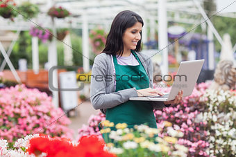 Woman doing stocktaking with laptop