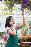 Woman looking at flowers in hanging basket