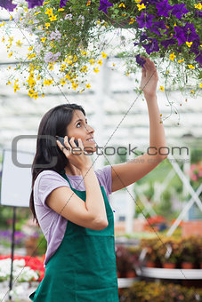 Woman looking at flowers in hanging basket