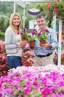 Couple holding purple plants and smiling