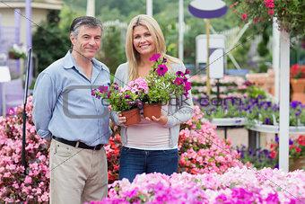 Joyful couple holding flowers