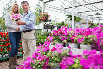 Happy couple holding pink flower in pot