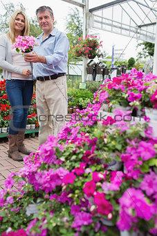 Happy couple standing in garden center