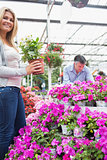 Woman holding a plant while man is looking through flowers
