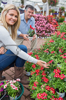 Couple crouching to look at flowers