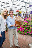 Happy couple holding ceramic flower pot