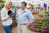 Couple smiling and looking at boot shaped flower pot