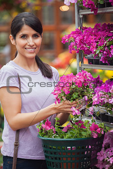 Black-haired woman holding pink flowers in garden center