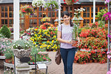 Woman carrying a daisy plant through garden center