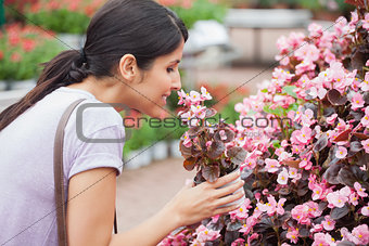 Black-haired woman smelling flower