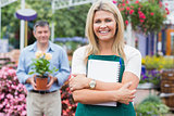 Woman holding a notepad with customer holding potted plant