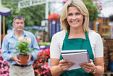 Smiling woman holding notepad with customer holding plant