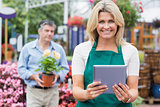 Smiling woman holding a tablet pc with customer holding plant behind