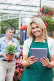 Cheerful florist holding a tablet pc in garden center
