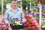 Man carrying boxes outside in garden center