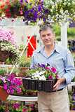 Smiling customer taking flower boxes outside