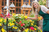 Garden center worker holding yellow flower