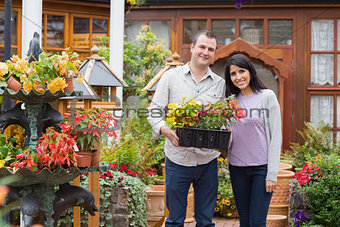Couple carrying tray of plants