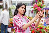 Brunette holding up pot of pink flowers