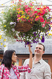 Couple touching the hanging flower basket