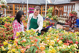 Customer and worker standing at a flowerbed