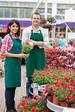 Two garden center workers with one holding flower pot