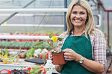 Blonde garden center worker holding flower pot