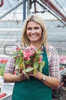 Blonde woman holding a flower working in garden center