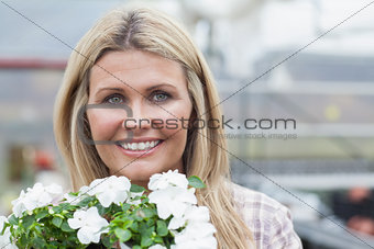 Smiling blonde holding white flowers