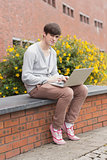Student sitting on wall with laptop
