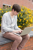 Young man using laptop outside