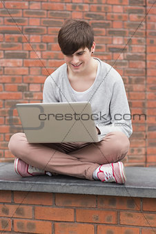 Man sitting cross legged and using laptop outside